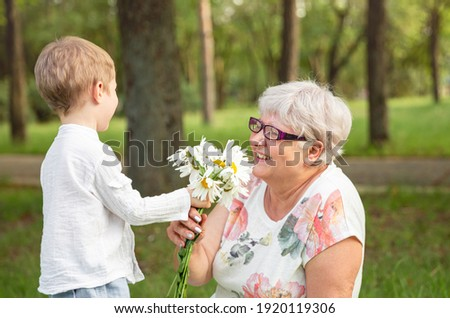 Beautiful boy giving a flower to grandma. Happy mothers day. Grandson and grandmother spending time together. Act of kindness to an elderly woman. Funny boy with flowers and his grandmother in park.