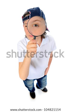Beautiful boy looking through a magnifying glass isolated on a white background