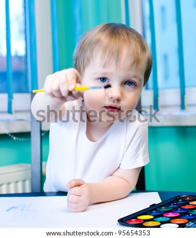 Beautiful boy painting with watercolors