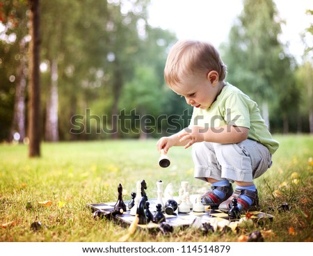 beautiful boy playing chess in summer park
