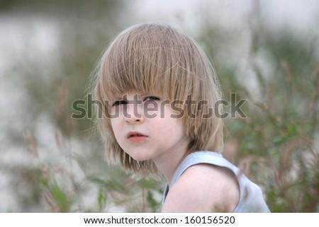 Beautiful boy portrait, playing in beach