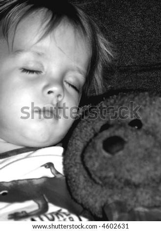 Beautiful Boy sleeping with his stuffed bear, black and white photo