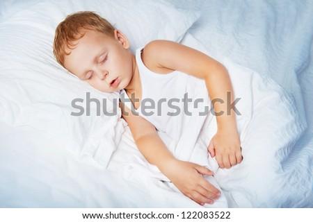 Beautiful boy sleeps in bed