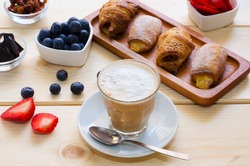 Beautiful  breakfast. Glass cup of coffee with milk served with crushed chocolate, different pastries, berries and raisins on the wooden background.
