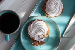 Beautiful breakfast tray setting from a cyan blue ceramic dishes on a white wooden breakfast tray in a daylight mood. Two white zephyr shortbread tarts and coffee