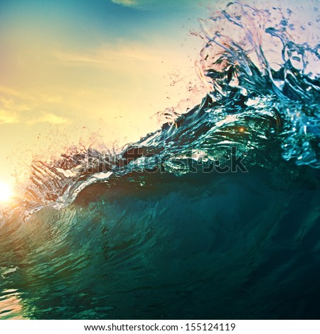 beautiful breaking surfing ocean wave closing at sunset time near tropical shore
