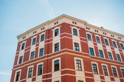 beautiful brick corner building with red facade and clean sky