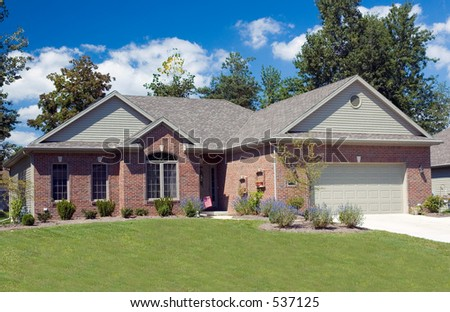 beautiful brick ranch home against a blue cloudy sky  stock photo