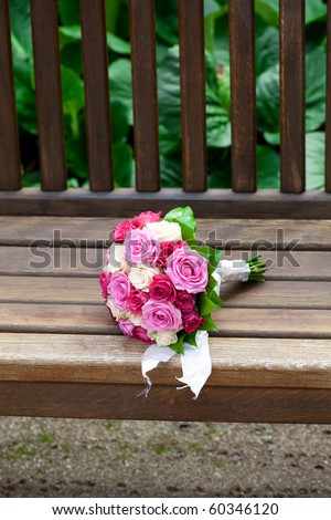 beautiful bridal bouquet lying on the wooden benches