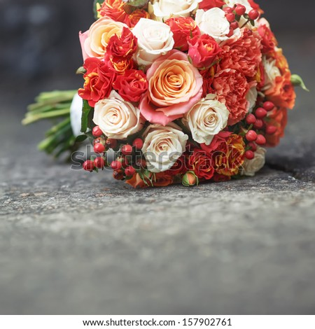Beautiful Bridal bouquet of various flowers on asphalt.