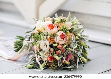 Beautiful bridal bouquet tied with silk ribbons and lace with a key in the form of heart. Roses and branches of an olive tree on the old vintage background . Wedding Accessories