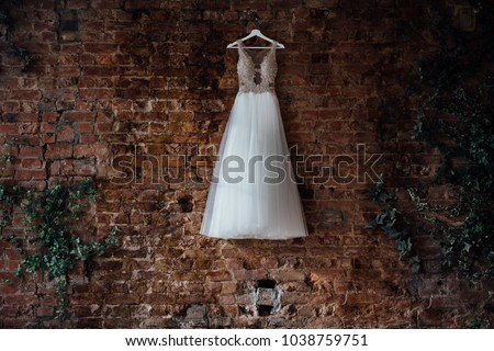beautiful bridal wedding dress hanging on a hanger on a brick wall in a loft studio. Nobody