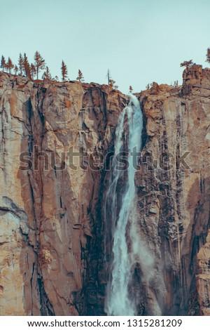 Beautiful Bridalveil Falls cut into the Granite of Yosemite National Park. Orange and tela style.
