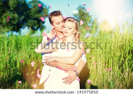 Beautiful bride and groom embracing. The petals in the form of hearts flying around a newlywed. Summer, love, wedding.