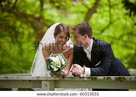 Beautiful bride and groom leaning over the railing for a quiet moment of happiness #60315031