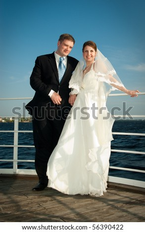 Beautiful bride and groom on the deck near river