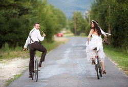 Beautiful bride and groom riding on the bikes