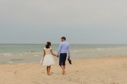 Beautiful bride and groom walking together on the beach.