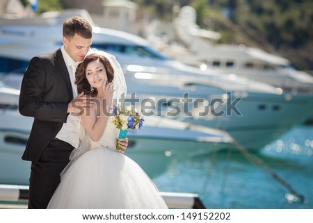 Beautiful bride and groom wedding couple dancing near sea yacht. Happy newlywed couple at wedding. Cheerful married couple standing on the beach. Monaco wedding. Cote de azure Gorgeous wedding outdoor