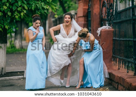 beautiful bride and her bridesmaids walking together. Funny moments on wedding day with best friends. Young woman with flowers. #1031043610