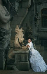 Beautiful bride beside chimeras and satire. Beauty and the Beast. Wedding theme.