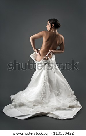 Beautiful bride dressing isolated in a dark background