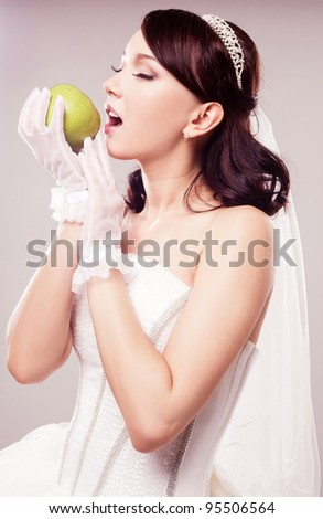 beautiful  bride eating an apple, isolated against grey studio background