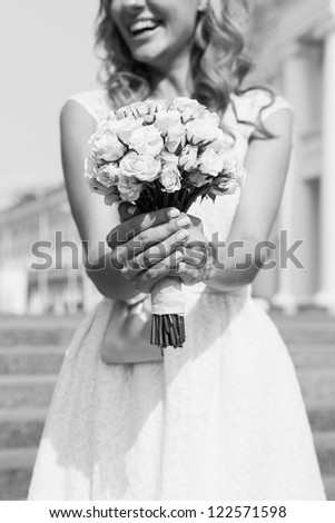 beautiful bride holding a wedding bouquet in hands, outdoors - stock photo