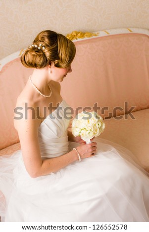 Beautiful bride holds a bridal bouquet, focus on wedding hairstyle