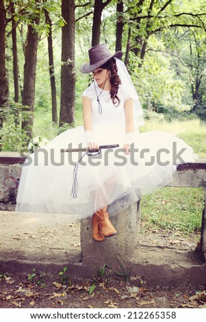 Beautiful bride in a cowboy hat and whip