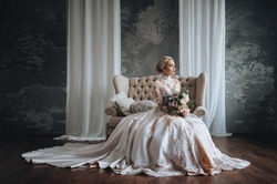 Beautiful bride in a cream wedding dress with a wedding bouquet, with orange and white flowers. Studio, gray background, modern, sofa, lace dress.