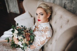 Beautiful bride in a lace dress with an original wedding bouquet in a vintage interior.