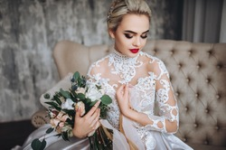 Beautiful bride in a white wedding dress with a wedding bouquet, with orange and white flowers. Studio, gray background, modern, sofa, lace dress.
