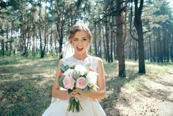 Beautiful bride in fashion wedding dress on natural background.The stunning young bride is incredibly happy. Wedding day. .A beautiful bride portrait in the forest.