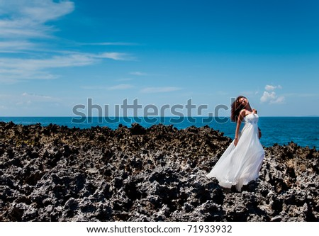 Beautiful bride in his dreams standing on a reef near the ocean