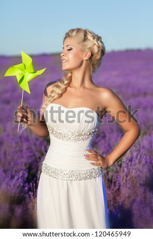 beautiful bride in luxurious wedding dress in purple lavender flowers. Fashion romantic stylish happy woman with blond hair. Smiling slim girl in sunset over summer lavenda waiting for groom -Provence