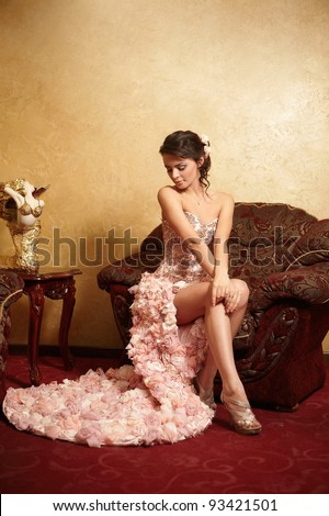 Beautiful bride in unusual wedding dress in the interior sitting in armchair