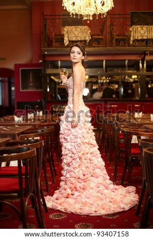 Beautiful bride in unusual wedding dress in the restaurant with cup of wine