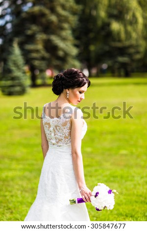 Beautiful bride in wedding dress and bridal bouquet, happy newlywed woman with wedding flowers, woman with wedding makeup and hairstyle. gorgeous young bride outdoors. Bride waiting for groom. bride