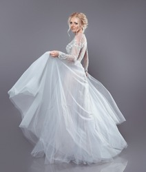 Beautiful bride in wedding flowing chiffon dress, Woman in long flying blowing gown. Stunning fashion model. Attractive blonde in fabric waving Cloth Flowing isolated on studio grey background.