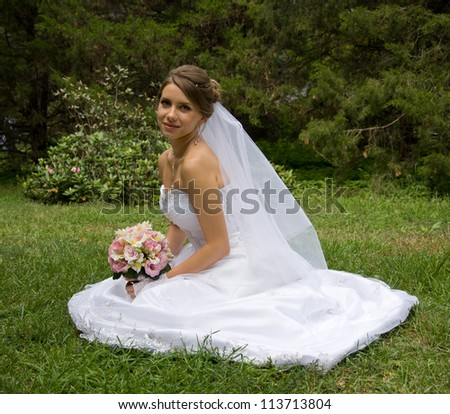 Beautiful bride in white dress sitting on green grass