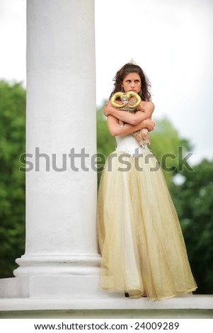 beautiful bride in white-golden dress with loved doll dreams of future