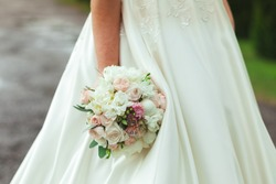 Beautiful bride in white wedding dress holding bouquet.