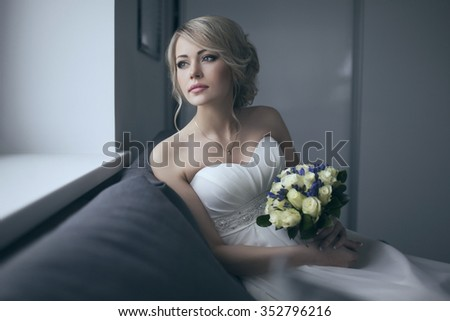 Beautiful bride in white wedding dress with bridal bouquet, with yellow and blue flowers