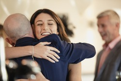Beautiful bride is sharing a dance with her proud father. They are laughing while hugging with their arms around each other.