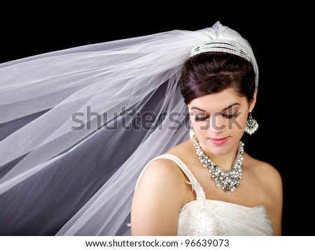Beautiful bride looking down with her veil blowing against the black background.