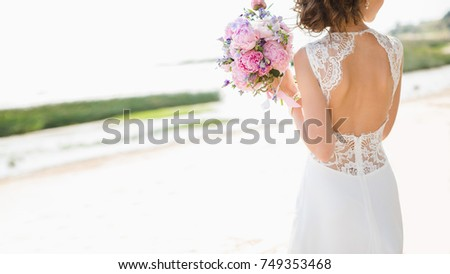 Beautiful bride on the seacoast. On the woman is a long wedding dress with lace and an open back. Bouquet in hands. Foto stock ©