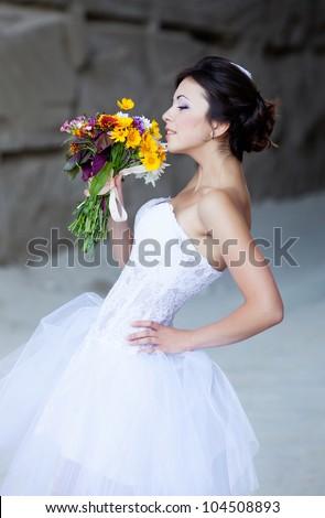 Beautiful bride outdoor portrait near high stone wall