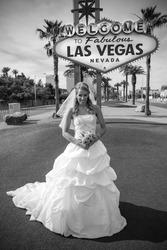 Beautiful bride poses at the las vegas sign
