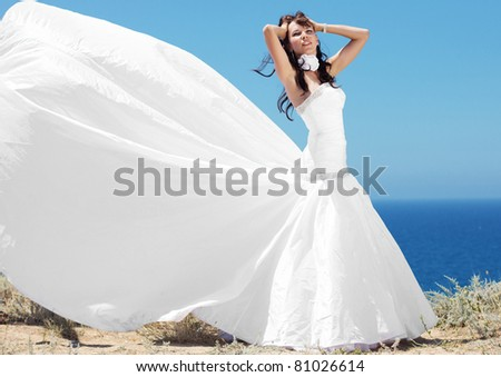 Beautiful bride posing at sea coast